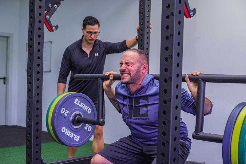 man squatting with smith machine